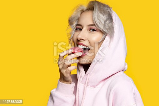 Portrait of sweet lady eating pink macaron and looking at camera. Pretty blonde girl and tasty cake. Food and pleasure concept. Isolated on yellow background