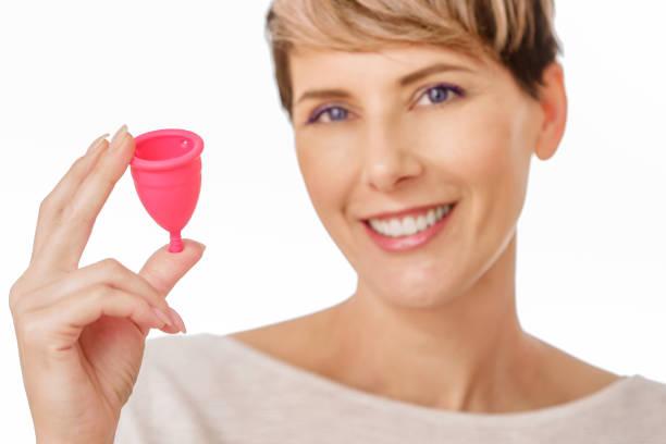 happy young woman holding a silicone menstrual cup - coppa mestruale foto e immagini stock