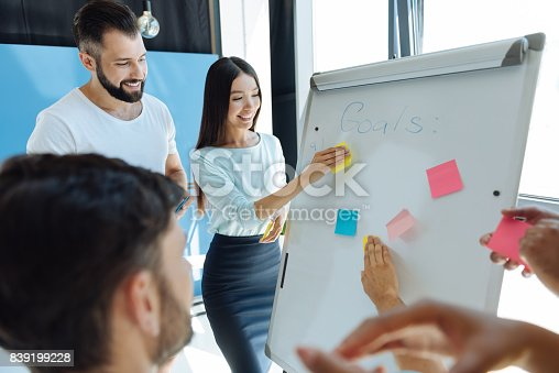 497451790 istock photo Happy young woman holding a sticky note 839199228