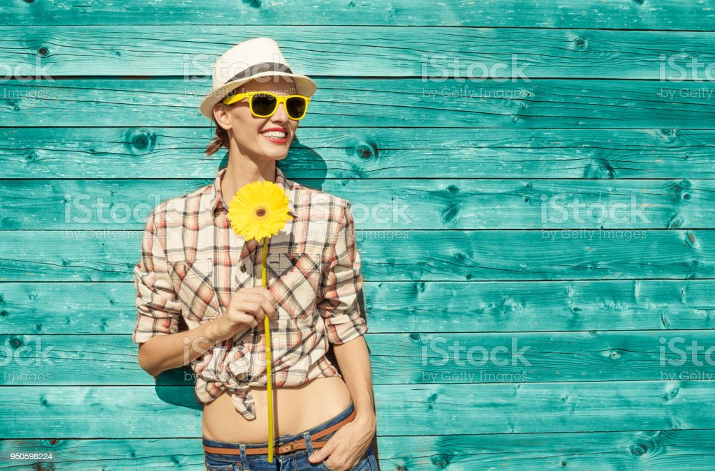 Happy young woman holding a sunflower. stock photo