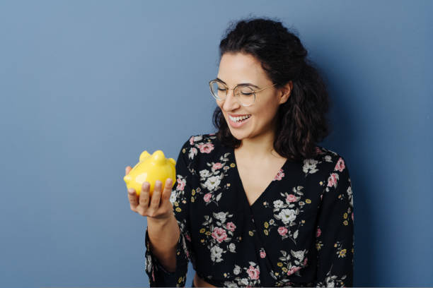 Happy young woman holding a yellow piggy bank stock photo