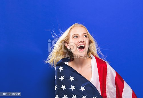 istock Happy young woman holding an American flag 1016316878