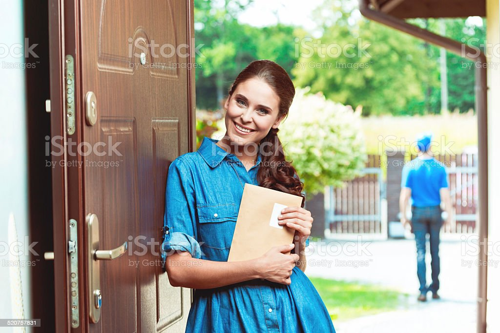 Happy young woman holding an envelope Young woman standing at the entrance of the house and holding an envelope in hands, postman in the background. 20-24 Years Stock Photo