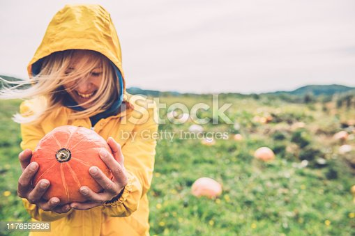 Happy Young Woman holding an Orange Pumpkin in hands