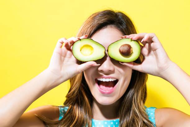 Happy young woman holding avocado halves stock photo
