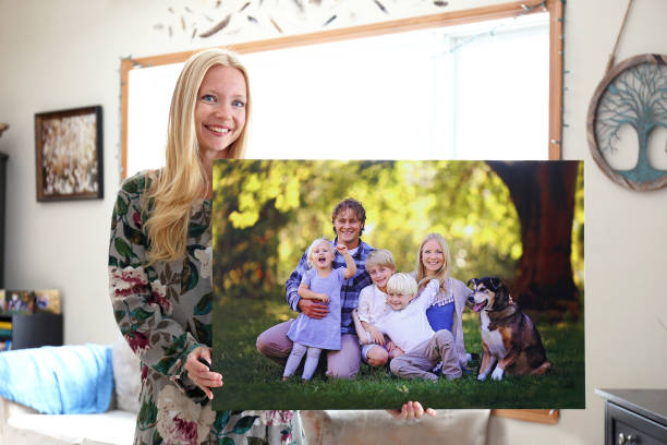 Happy Young Woman Holding Canvas Print of Family Portrait stock photo
