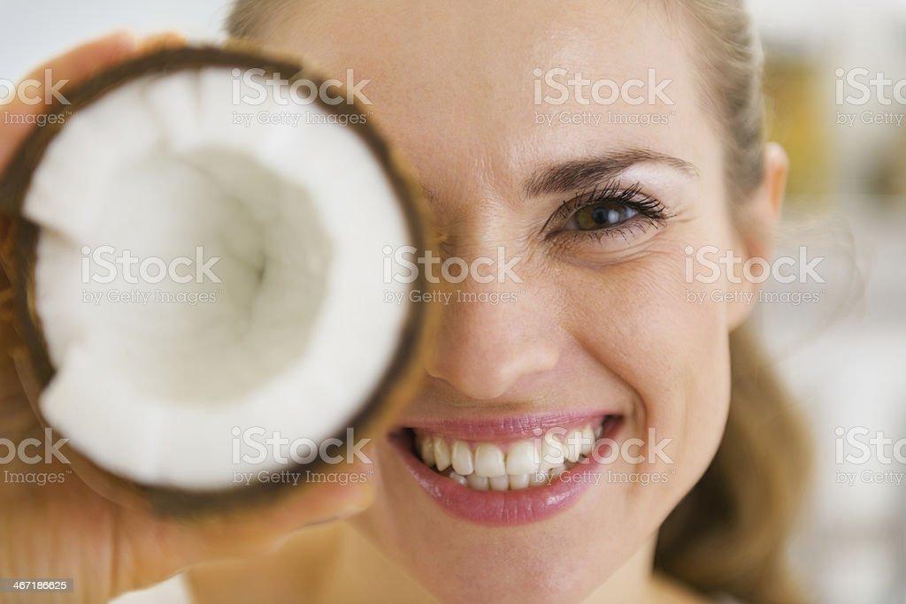 Glückliche junge Frau mit Kokosnuss Stück vor Augen – Foto