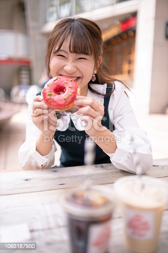 Happy young woman holding doughnut at open cafe