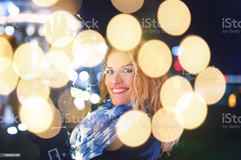 Happy young woman holding fairy lights at cold night in city, waiting...