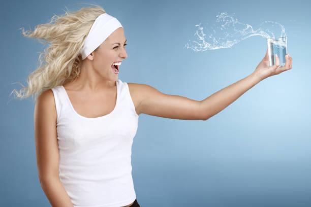 Glückliche junge Frau hält Glas erfrischenden Wasser – Foto