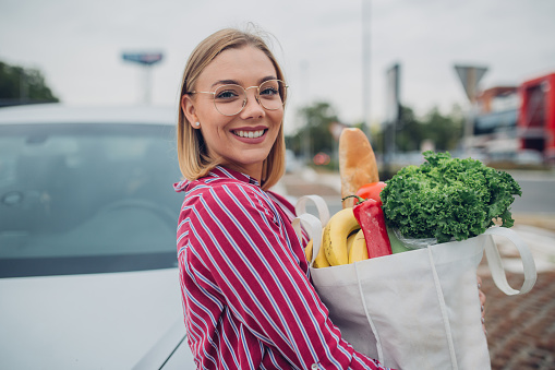 istock Happy young woman holding groceries in reusable bag 1177331068