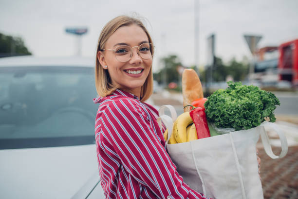 Happy young woman holding groceries in reusable bag stock photo