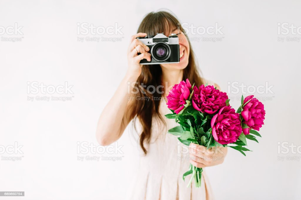 Happy young woman holding in hands peony bouquet and shooting on old vintage camera. Sweet romantic moment. Smiling woman foto de stock royalty-free