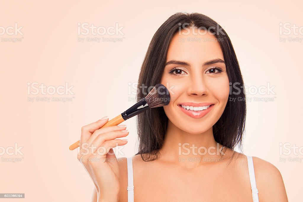 Happy young woman holding makeup brush on pink background stock photo