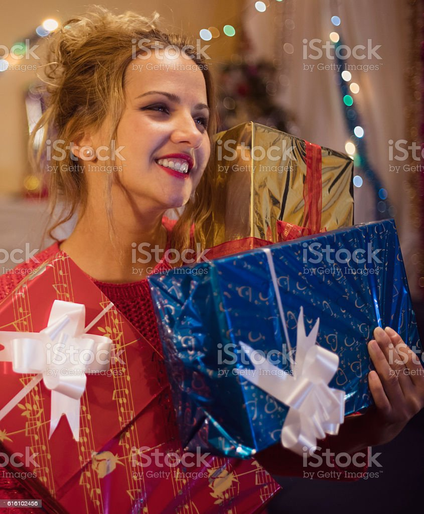Happy young woman holding many present boxes in snowy night. stock photo