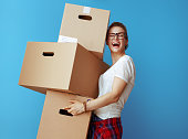 istock happy young woman holding pile of cardboard boxes on blue 1129171875
