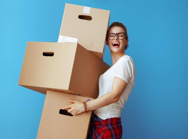 glad ung kvinna håller hög av kartonger på blå - flyttlådor bildbanksfoton och bilder