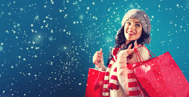 Happy young woman holding shopping bags Happy young woman holding shopping bags in a snowy night buying stock pictures, royalty-free photos & images