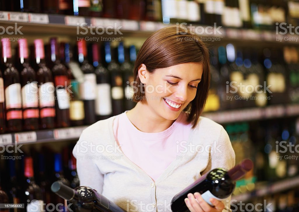 Happy young woman holding two bottles of wine royalty-free stock photo