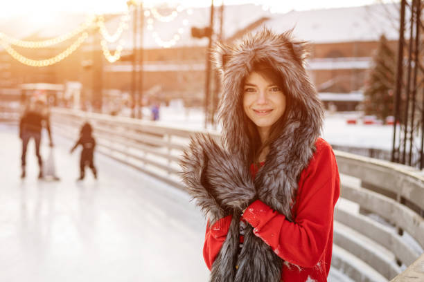 Happy young woman in a wolf hat in winter at the ice rink poses in a red sweater outside in the afternoon stock photo