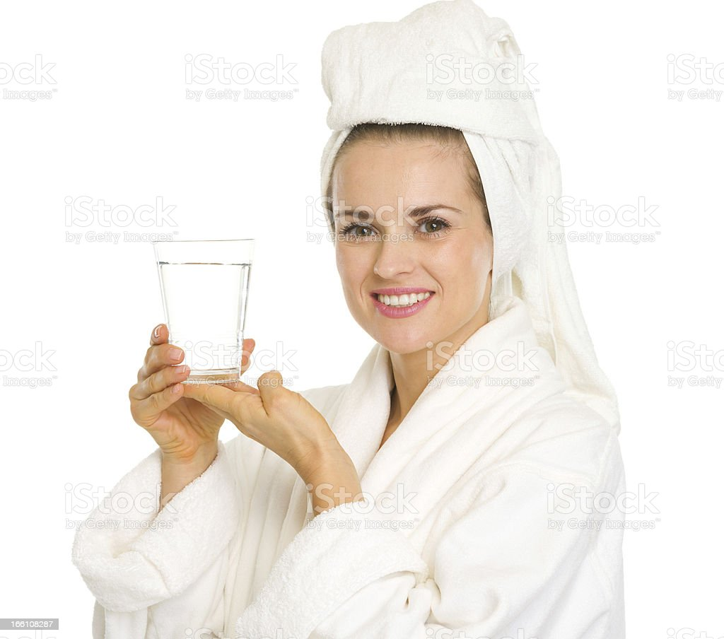 Happy young woman in bathrobe holding glass of water royalty-free stock photo