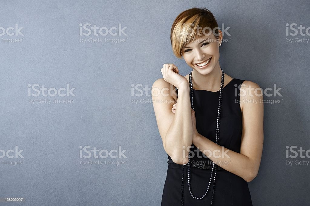 Happy young woman in black dress and pearls stock photo