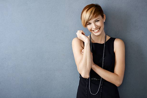 Happy young woman in black dress and pearls Portrait of happy young woman in black dress and pearls on grey background.. short hair stock pictures, royalty-free photos & images