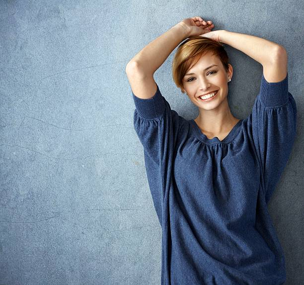 Happy young woman in blue jeans posing at wall stock photo