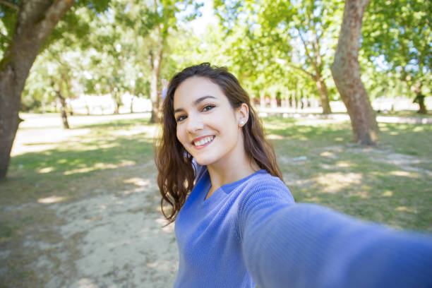 happy young woman in blue sweater talking selfie in park - selfie foto e immagini stock