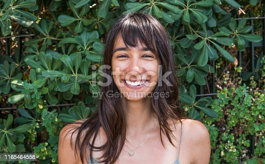 Happy young woman in front of green leafs