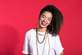 Studio portrait of happy hip-hop style young latin woman wearing gold jewellery, laughing against red background.