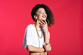 Portrait of happy hip-hop style young latin woman wearing gold jewellery, standing against red background.