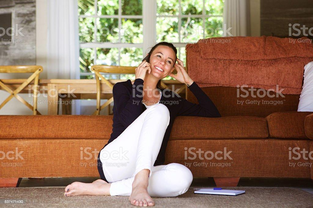 Heureuse jeune femme dans la salle de séjour à l'aide de téléphone portable - Photo