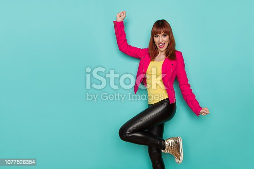 Happy young woman in pink jacket, black leather trousers and gold sneakers is standing on one leg, shouting and rising arm. Three quarter length studio shot on turquoise background.