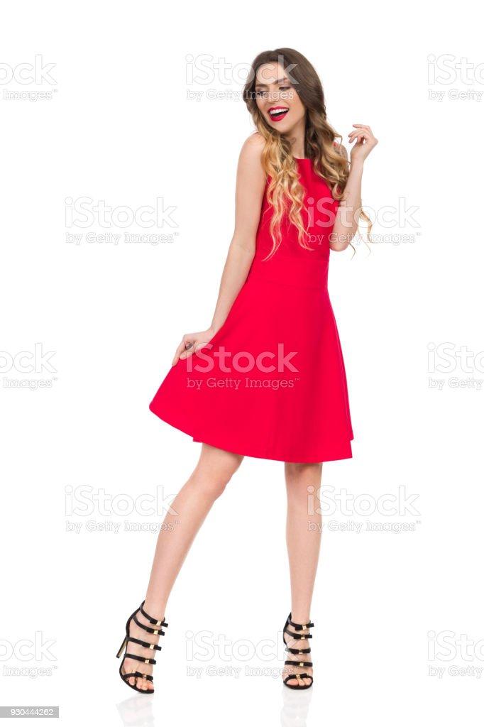e31b1f83a85 Heureuse jeune femme en robe rouge et des talons hauts cherche loin photo  libre de droits