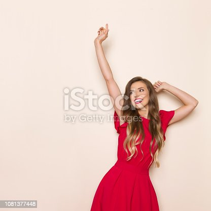 Beautiful young woman in red dress is looking away, smiling and holding arms raised. Three quarter length studio shot on beige background.