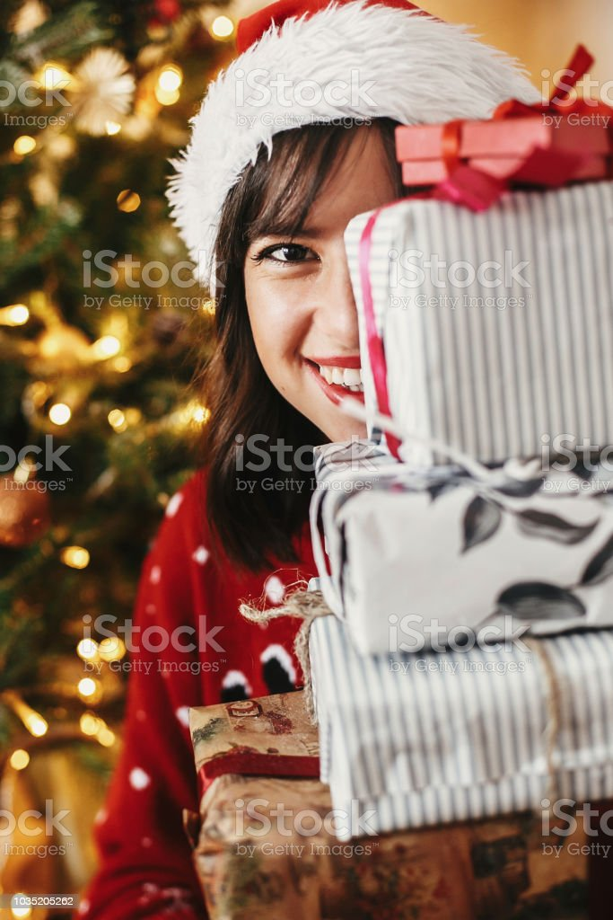 happy young woman in santa hat holding pile of gift boxes at golden...