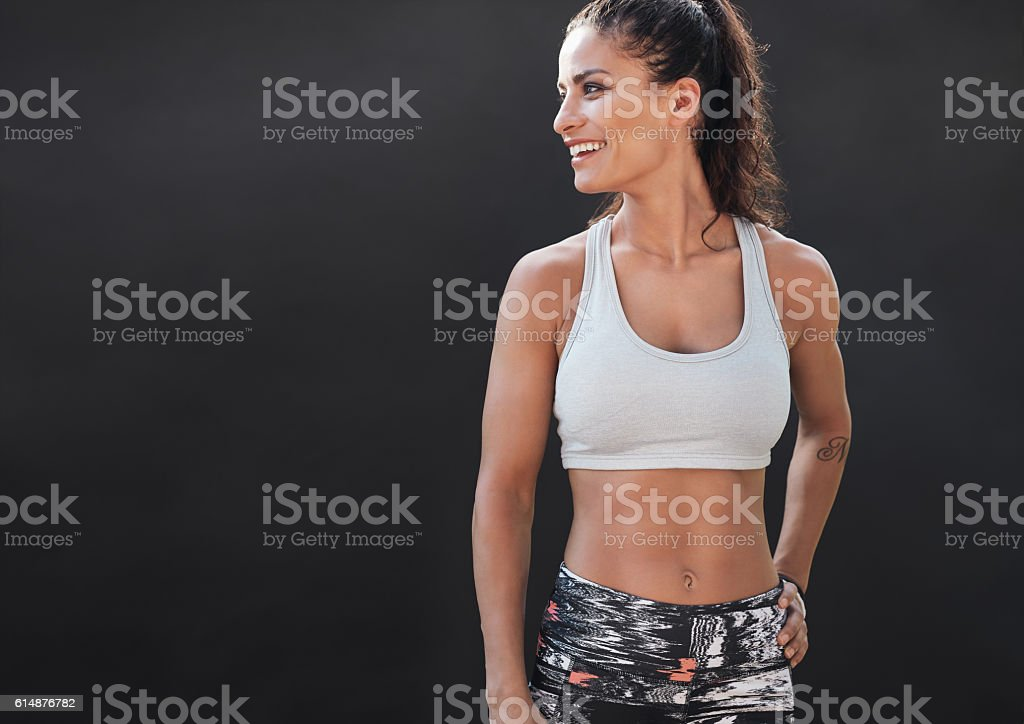 Happy young woman in sports clothing smiling stock photo