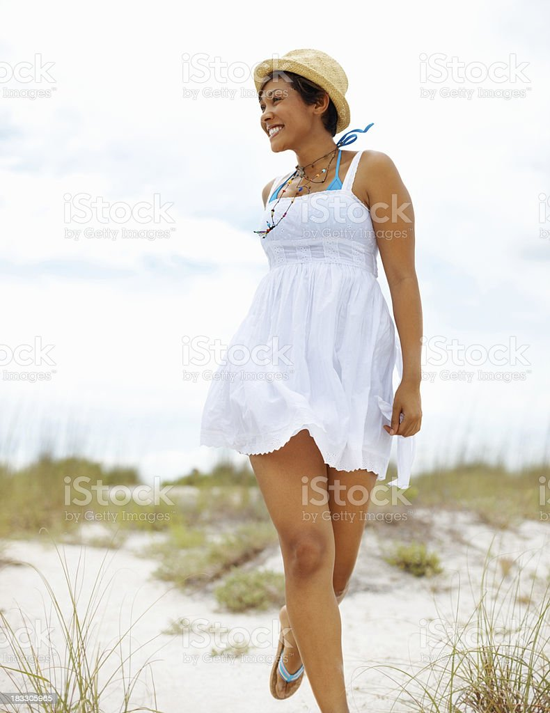 Happy, young woman in sundress running on the beach royalty-free stock photo