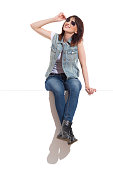 Young woman in sunglasses, jeans vest and black boots is sitting on a top, looking away and smiling. Full length studio shot isolated on white.