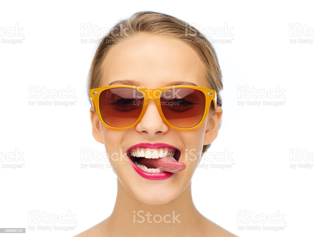 happy young woman in sunglasses showing tongue stock photo