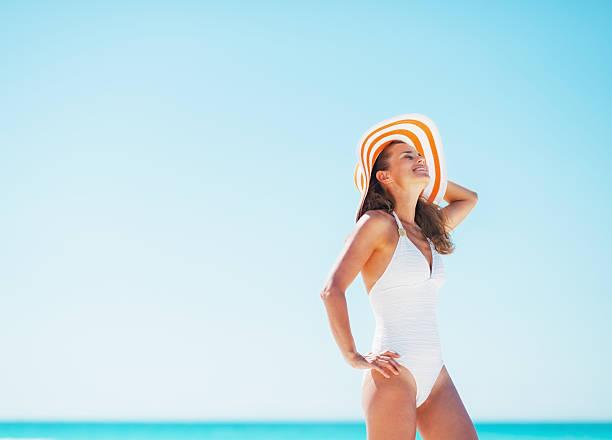 Glückliche junge Frau in Badeanzug und Strand Hut Entspannen auf – Foto