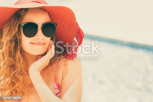 1062333060istockphoto Happy young woman in swimsuit at swimming pool. 1019716046