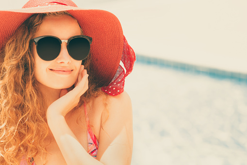 1062333060 istock photo Happy young woman in swimsuit at swimming pool. 1019716046