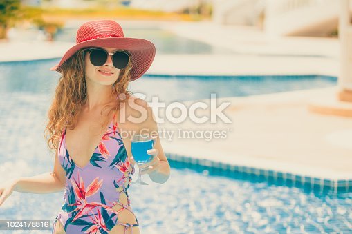 1062333060istockphoto Happy young woman in swimsuit at swimming pool. 1024178816