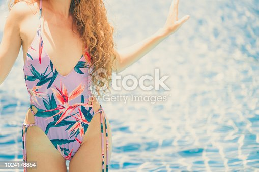 1062333060istockphoto Happy young woman in swimsuit at swimming pool. 1024178854