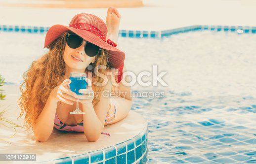 1062333060istockphoto Happy young woman in swimsuit at swimming pool. 1024178910
