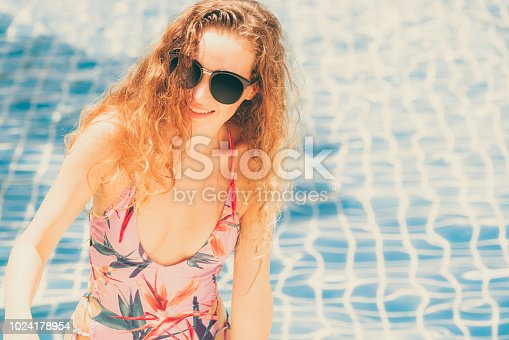1062333060istockphoto Happy young woman in swimsuit at swimming pool. 1024178954