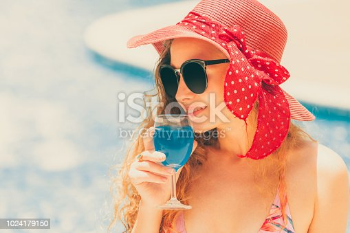 1062333060istockphoto Happy young woman in swimsuit at swimming pool. 1024179150