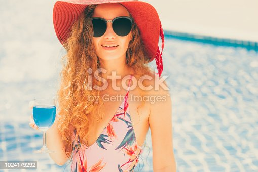 1062333060istockphoto Happy young woman in swimsuit at swimming pool. 1024179292